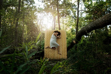Heather Evans Smith WOMAN LYING UPRIGHT ON MATTRESS IN FOREST