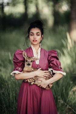 Jovana Rikalo WOMAN STANDING IN COUNTRYSIDE HOLDING FAWN