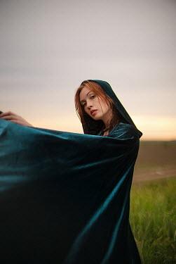 Alexandra Bochkareva WOMAN IN HOODED CAPE BY COUNTRY ROAD