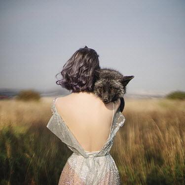 Alexandra Bochkareva GIRL STANDING IN COUNTRYSIDE HOLDING FOX