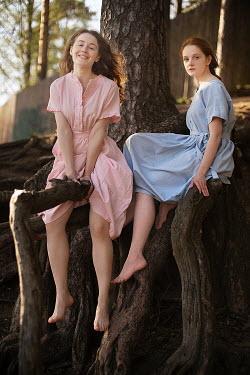Alexandra Bochkareva TWO BAREFOOT GIRLS SITTING ON TREE ROOTS