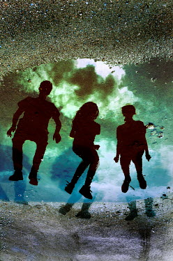 Ute Klaphake THREE SILHOUETTED TEENAGERS REFLECTED IN PUDDLE