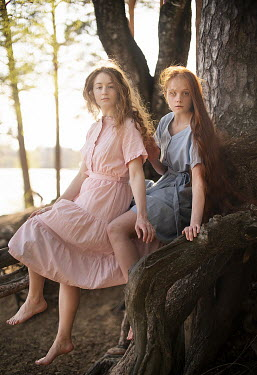 Alexandra Bochkareva TWO GIRLS SITTING ON TREE ROOTS BY LAKE