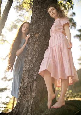 Alexandra Bochkareva TWO YOUNG GIRLS STANDING BY TREE
