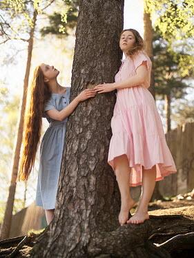 Alexandra Bochkareva TWO GIRLS HOLDING TREE TRUNK