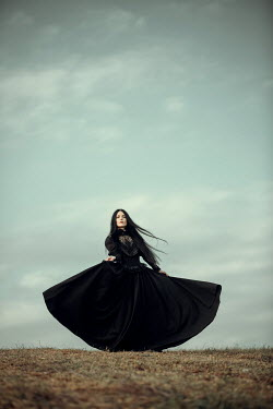 Magdalena Russocka historical woman in black dress standing in field