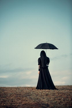 Magdalena Russocka historical woman in black dress with umbrella standing in field