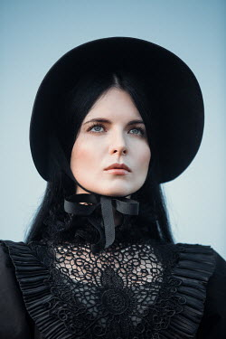Magdalena Russocka close up of historical woman in black dress and bonnet outside