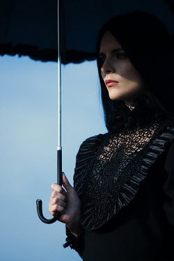 Magdalena Russocka close up of historical woman in black dress with umbrella outside