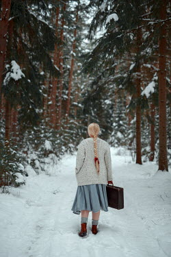 Nathalie Seiferth BLONDE GIRL ON SNOWY COUNTRY LANE WITH SUITCASE