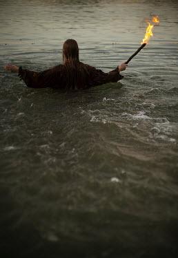 Alexandra Bochkareva WOMAN IN WATER HOLDING BURNING STICK