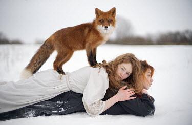 Alexandra Bochkareva TWO WOMEN LYING IN SNOWY COUNTRYSIDE WITH FOX