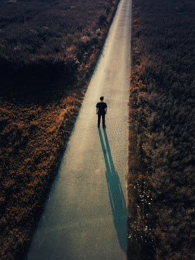 Magdalena Russocka modern man standing on country road at sunset from above