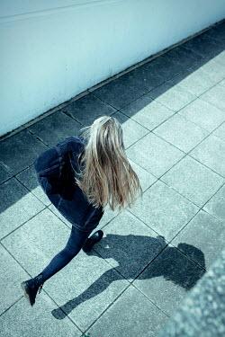 Shelley Richmond BLONDE GIRL RUNNING IN CONCRETE PASSAGEWAY