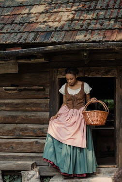 Magdalena Russocka historical african woman carrying basket coming out from old cabin