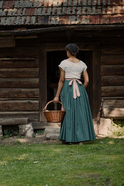 Magdalena Russocka historical african woman carrying basket standing by old cabin