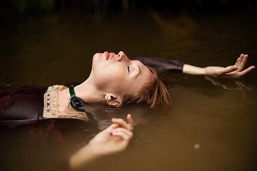 Alexandra Bochkareva WOMAN FLOATING IN MUDDY RIVER