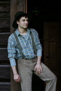 Magdalena Russocka young vintage man leaning against door of old cabin