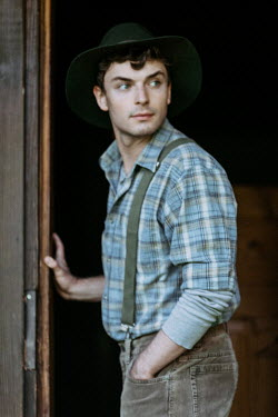 Magdalena Russocka young vintage man standing by door of old cabin