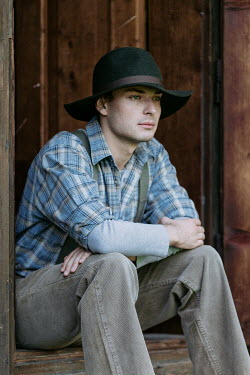 Magdalena Russocka young vintage man sitting on threshold of old cabin