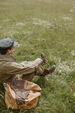 Shelley Richmond MAN IN FLYING SUIT SITTING ON GRASS