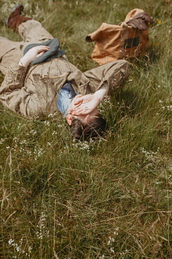Shelley Richmond MAN IN FLYING SUIT LYING ON GRASS