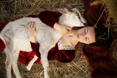 Alexandra Bochkareva GIRL LYING ON STRAW HUGGING GOAT