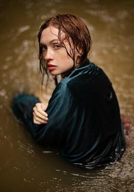 Alexandra Bochkareva WOMAN WITH CAPE SITTING IN RIVER