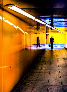 Adrian Leslie Campfield SILHOUETTED MAN CARRYING BAG IN MODERN PASSAGEWAY