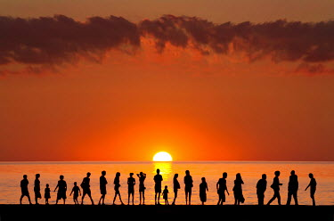 Adrian Leslie Campfield SILHOUETTED CROWD OF PEOPLE ON BEACH AT SUNSET