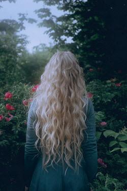 Irina Orwald WOMAN WITH LONG BLONDE HAIR IN SUMMERY GARDEN