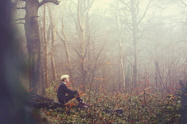 Eve North BLONDE MAN SITTING IN FOGGY FOREST