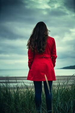 Marie Carr WOMAN IN RED COAT STANDING BY BEACH