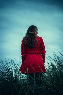 Marie Carr WOMAN IN RED COAT STANDING IN LONG GRASS