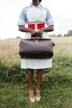 Matilda Delves NURSE STANDING IN COUNTRYSIDE HOLDING BAG
