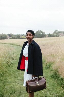 Matilda Delves NURSE STANDING IN COUNTRYSIDE HOLDING CASE