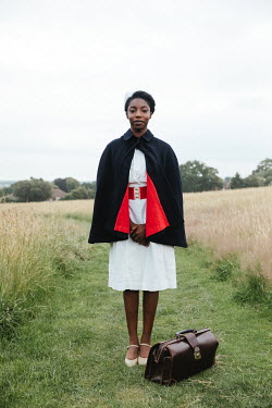 Matilda Delves NURSE STANDING IN COUNTRYSIDE WITH CASE