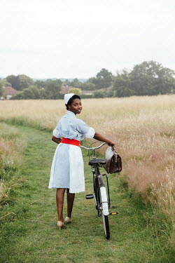 Matilda Delves NURSE IN COUNTRYSIDE PUSHING BICYCLE