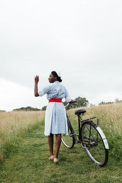 Matilda Delves NURSE WITH BICYCLE WAVING IN COUNTRYSIDE