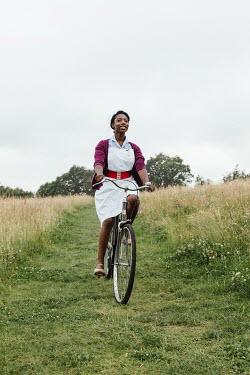 Matilda Delves HAPPY NURSE RIDING BICYCLE IN COUNTRYSIDE