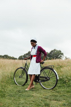 Matilda Delves NURSE WITH BICYCLE STANDING IN COUNTRYSIDE