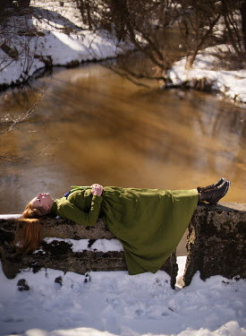 Alexandra Bochkareva WOMAN WITH RED HAIR LYING BY RIVER WITH SNOW