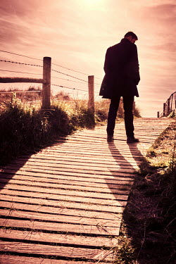 CollaborationJS MAN IN COAT STANDING ON WOODEN PATHWAY