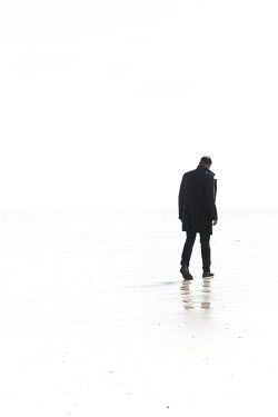 CollaborationJS MAN IN COAT WALKING ON BEACH