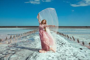 Katerina Klio WOMAN WITH PINK SILK STANDING ON BEACH