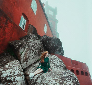 Katerina Klio WOMAN SITTING ON ROCKS OUTSIDE CASTLE