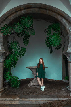 Katerina Klio GIRL WITH RED HAIR BY ARCHWAY WITH PLANT