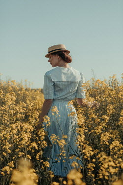 Magdalena Russocka young retro woman standing in rapeseed field