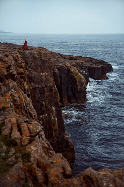 Nathalie Seiferth WOMAN IN CAPE STANDING ON CLIFFS BY SEA