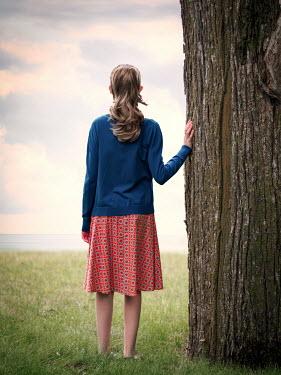 Elisabeth Ansley GIRL STANDING BY TREE WATCHING SEA